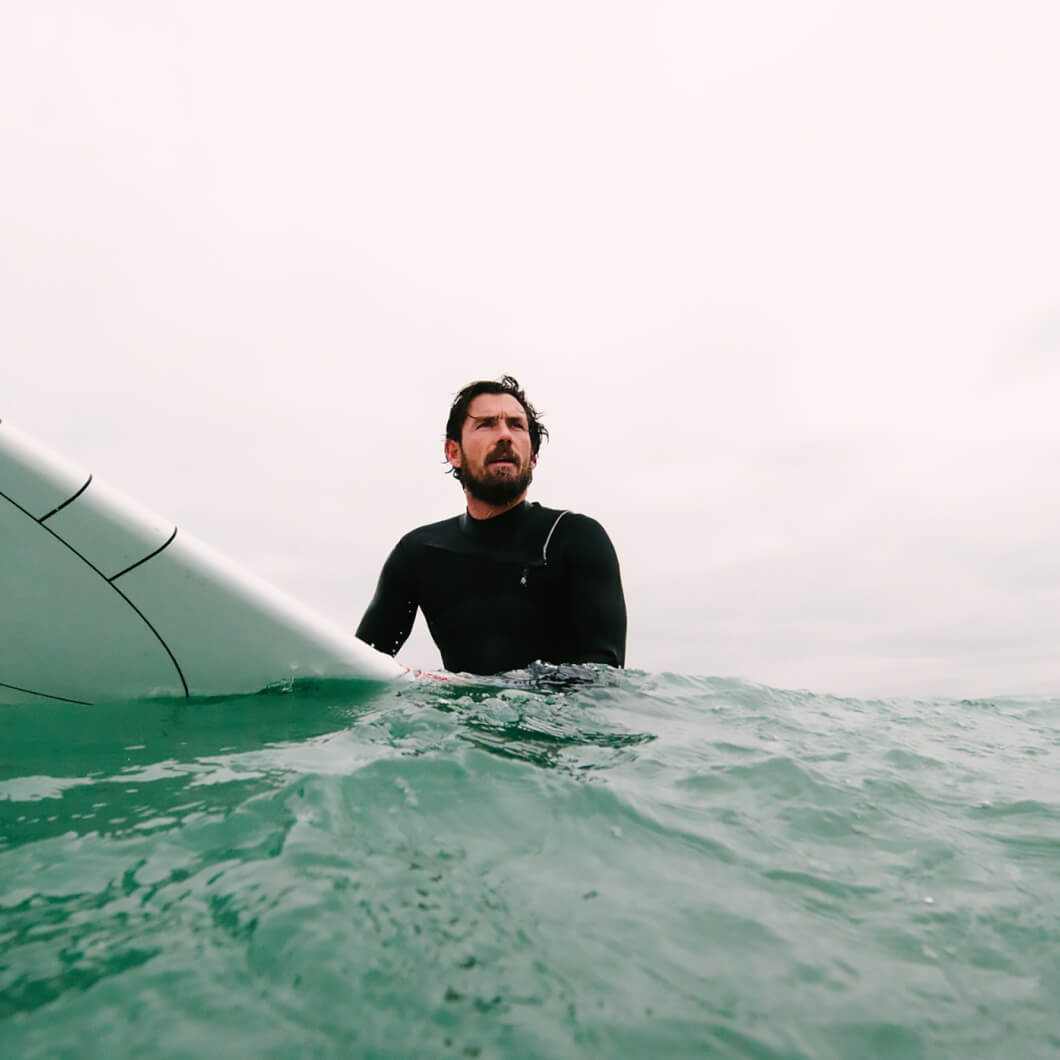 Bearded man in the sea with a surfboard