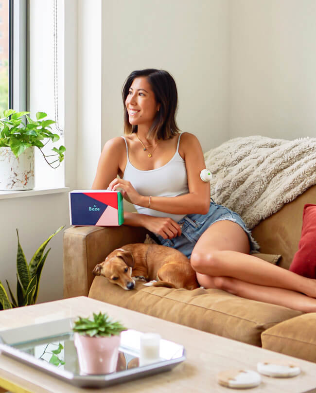 Female sitting on a couch with her dog holding the Baze Nutrient Test Kit