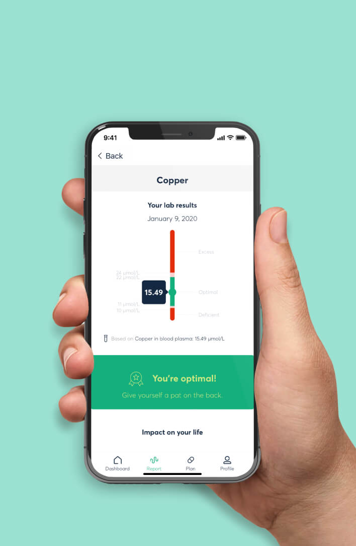 A male hand holding a phone that is showing the Baze app. The app is displaying lab results for the micronutrient Copper