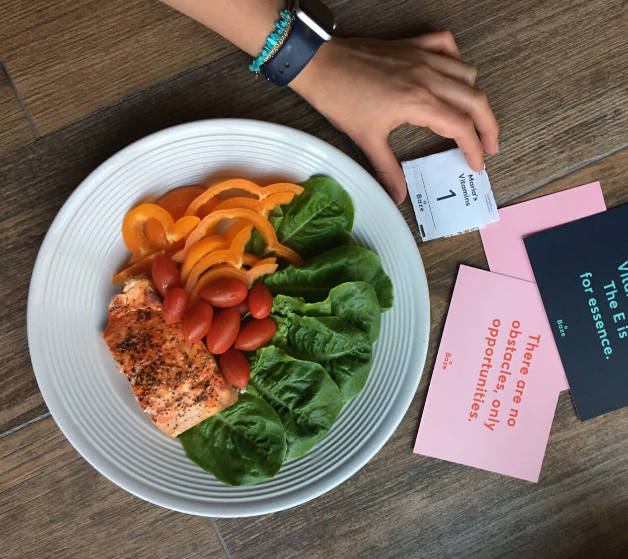 A female hand holding a daily supplement pack titled 'Maria's Vitamins' with a plate of colorful vegetables and salmon sitting in the background